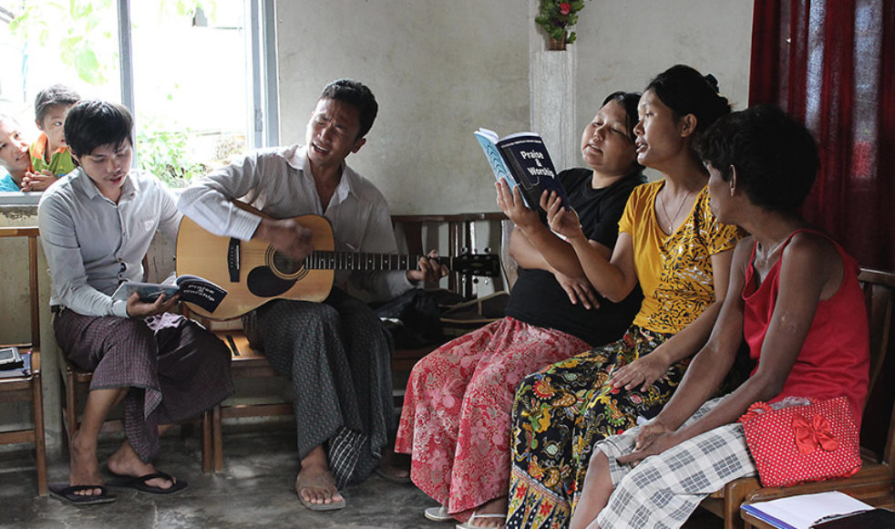 Htetlin, före detta buddhist men som nu varit kristen i ett år, leder lovsången under en av husförsamlingsbesöken.