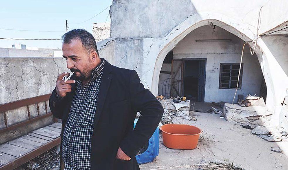 Yasir tänder en cigarett och berättar: »Min fru hade tänkt att följa med idag men hon var rädd för hur hon skulle reagera när hon såg hemmet och staden, så hon ändrade sig i sista sekund.«