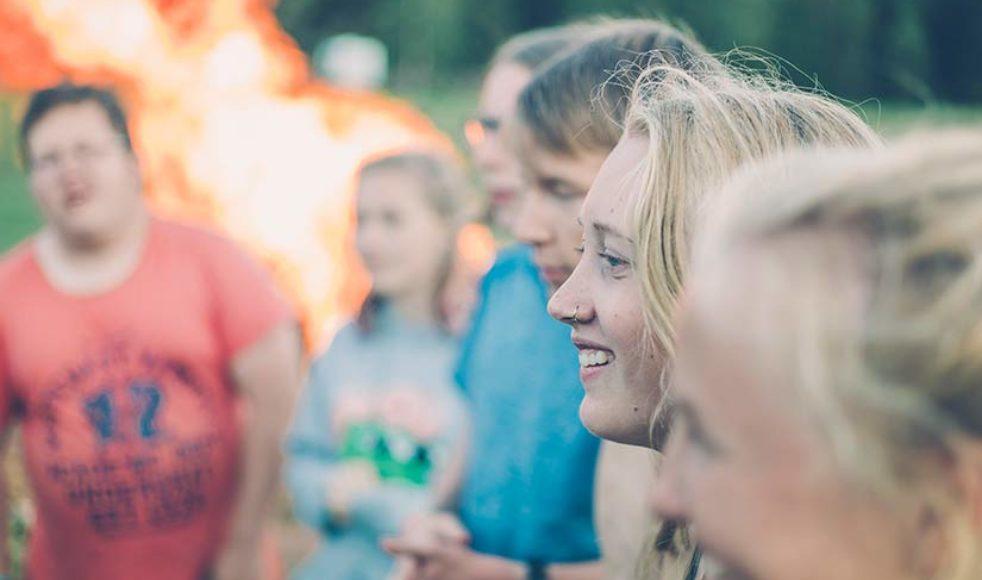 Malva Wärnsberg sjunger sånger tillsammans med sina vänner runt lägerelden.