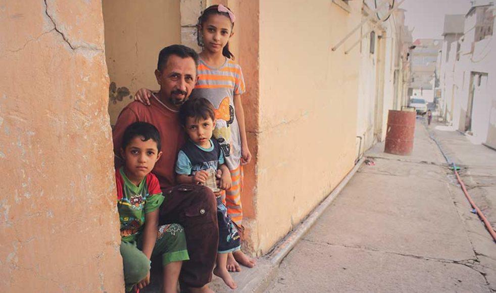 Amar Ahmad Abdullah med sina tre barn i dörren till deras hus i västra Mosul.