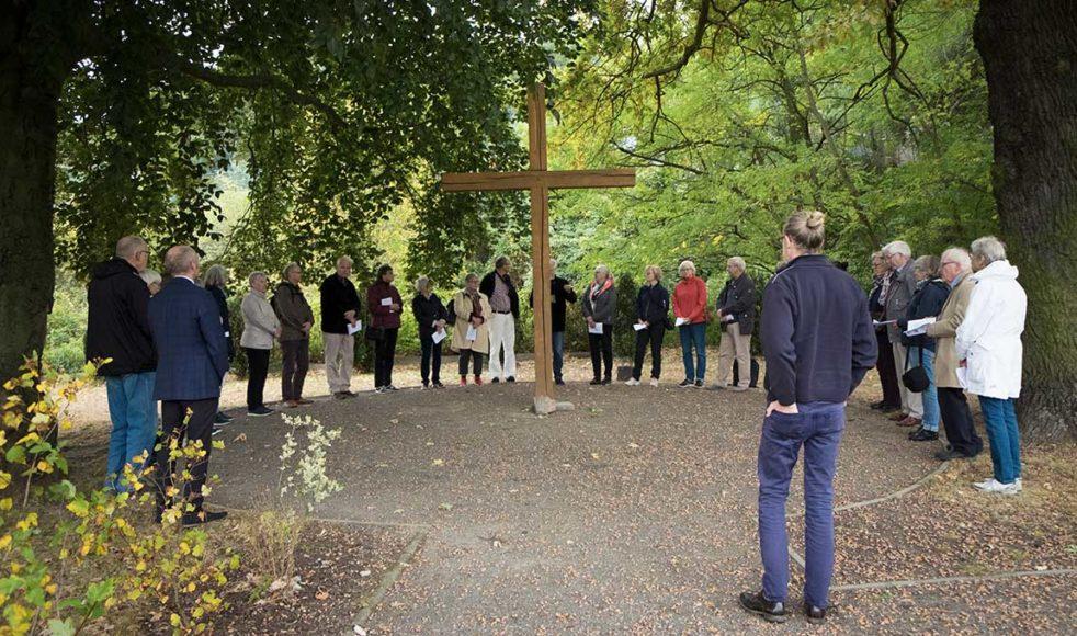 I trädgården i Szczecin samlas resesällskapet för andakt i Bonhoeffers anda runt korset.