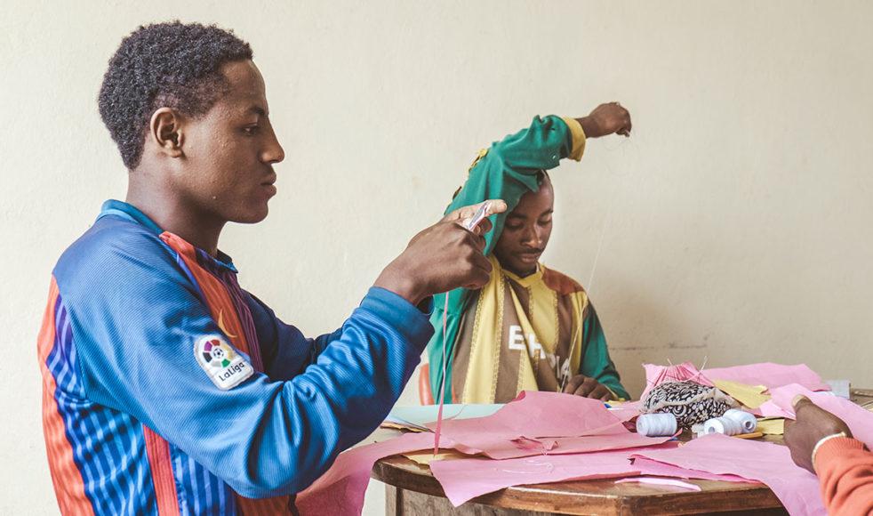 Melaku Abebe, närmast kameran, är född i södra Etiopien. En släkting lovade honom ett nytt liv i Addis, men Melaku blev i stället tvingad till olika former av arbete utan ersättning. Han jobbade så hårt att han blev sjuk och han svimmade ofta. Hos Hope for Children har hans hälsa återställts helt och nu lär han sig att väva. Han är en av de mest dedikerade lärlingarna och i framtiden drömmer han om att starta eget företag i sin hemstad.