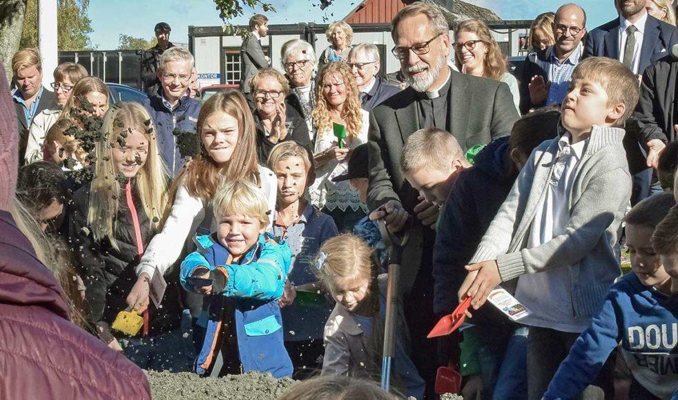 Kyrkoherde Lars Hjort tar det första spadtaget tillsammans med barn från området. Bild: Maria Lokrantz