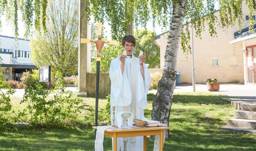 Församlingsherde Sara Nillson Edström leder en utomhusmässa intill Lötenkyrkan. Bild: Johan Ericson