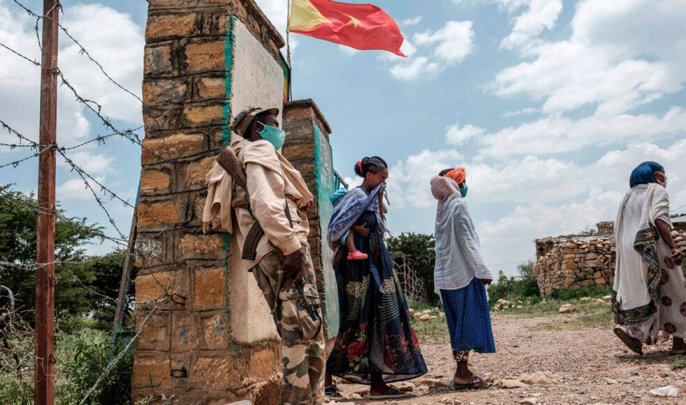 En beväpnad vakt utanför en av vallokalerna under det osanktionerade val som hölls i Tigray-regionen i september. Ovanför vajar regionens fana. Bild: TT