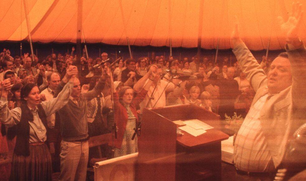 Arne Imsen predikar i ett fullsatt tält under en sommarkonferens i slutet av 1970-talet. Bilder: Hans Brynte