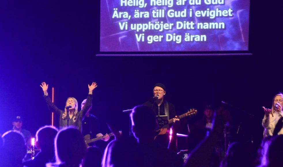 Sanna Välipakka och Alexander Forsberg leder lovsång på ett möte med Hope for this nation, en ekumenisk tillbedjansrörelse.