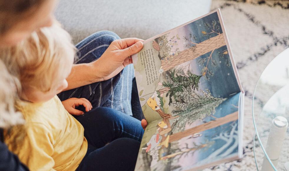 Sonen Olle lyssnar spänt när mamma Amanda högläser ur barnboken I en helt vanlig skog.